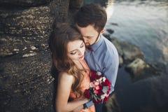 Die Hochzeitspaare, die auf Felsen küssen und umarmen, nähern sich blauem Meer Lizenzfreie Stockfotos