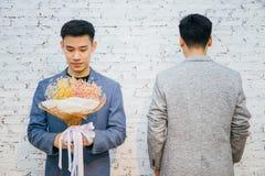 Die homosexuellen Paare, die einen Blumenstrauß von Blumen halten, bereiten vor, um zu geben seinem Partner für spezielle Gelegen lizenzfreie stockfotografie