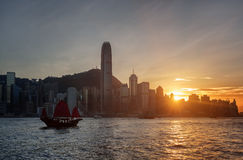 Die Hong Kong Island-Skyline bei Sonnenuntergang Segelschiff in der Bucht Stockbild