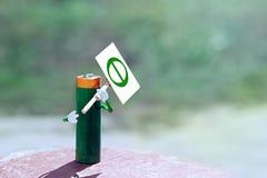 Die humanisierte Zahl, die von AA-Batterie gemacht wird, hält im Handplakat mit dem Symbol des Tages der Erde Glücklicher Mann ge Lizenzfreies Stockbild