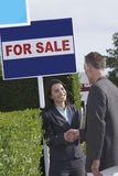 Die Immobilienagentur, die Hände mit Mann dazu für Verkauf rüttelt, unterzeichnet Stockbild