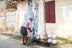 Die Indien-Männer pumpen Wasser zum Behälter für Haus stockbilder