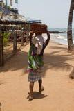 Die indische Frau in den Steinen eines Saris für das Errichten auf dem Kopf auf einem Strand Indien-goa Lizenzfreie Stockfotografie