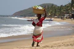 Die indische Frau in einem Sari trägt Frucht auf dem Kopf auf einem Strand Indien-goa Lizenzfreies Stockfoto