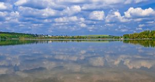 Die Insel unter dem See, auf dem hohe grüne Bäume gegen einen blauen Himmel mit Wolken wachsen Sie stockbild