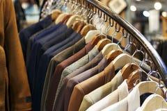 Die Jacken der stilvollen Männer auf Aufhängern im Speicher, Nahaufnahme stockfoto