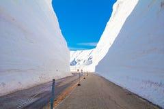 Die Japan-Alpen oder die Schneegebirgswand von Tateyama Kurobe alpin am Sonnenscheintag mit Hintergrund des blauen Himmels ist ei stockfotografie