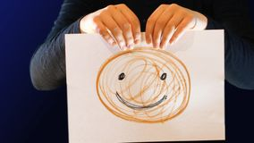 Die Jugendliche, die ein Papierzeichen in ihrer Hand mit einem Lächeln oben gezeichnet hält, reißt es auseinander und zeigt ihr u lizenzfreies stockfoto