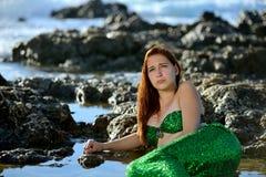 Die Jugendliche im grünen glänzenden Meerjungfraukostüm liegt bei Sonnenuntergang im Wasser unter den Steinen auf der Küste und s stockfoto