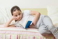 Die Jugendliche 10 Jahre alt in der Hauptkleidung liest ein Buch auf dem Bett in ihrem Raum Lizenzfreie Stockfotografie