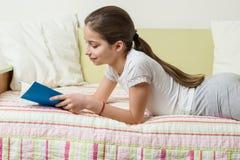 Die Jugendliche 10 Jahre alt in der Hauptkleidung liest ein Buch auf dem Bett in ihrem Raum Stockbilder