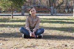 Die Jugendliche sitzt auf der Erde im Park Stockbilder