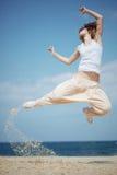 Die Jugendliche springend auf Strand Stockfotografie