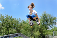 Die Jugendliche springend in die Luft auf Rollerblades lizenzfreie stockfotos
