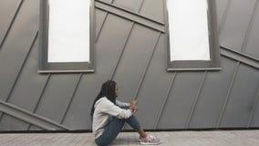 Die junge Afroamerikanerfrau, die traurig schaut und beschließen Musik, um an ihrem Telefon zu hören Grauer Wandhintergrund stock video footage