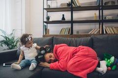 Die junge alte Mutter erfährt postnatale Depression Traurige und müde Frau mit PPD Sie möchte nicht mit ihr spielen stockbild