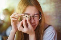 Die junge asiatische Frau, die eine hölzerne vorbildliche Kamera anhebt, um vom Auge zu konfrontieren, mögen eine Kamera, Spiel n Lizenzfreie Stockfotos