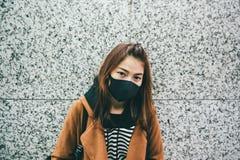 Die junge asiatische Frau, die eine schwarze Mundmaske als sie trägt, leidet unter schwerer Luftverschmutzung stockfotos