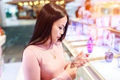 Die junge asiatische zutreffende Frau und beschließen, Parfüm im zollfreien Speicher am internationalen Flughafen zu kaufen lizenzfreie stockfotos