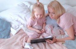 Die junge attraktive blonde Frau, die ein Buch auf Tablette ihre kleine reizend Tochter im Rosa liest, kleidet das Legen auf Bett Stockfotos