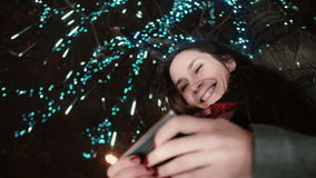 Die junge attraktive Frau, die Smartphone nachts die schneebedeckte Heilige Nacht steht unter einem Baum verziert wird mit dem Fu Stockfotos