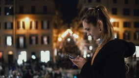 Die junge attraktive Frau, die im Stadtzentrum am Abend steht und benutzen den Smartphone Menge und Lichter auf dem Hintergrund Lizenzfreie Stockfotografie