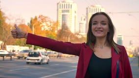 Die junge attraktive Frau, die nach einer Fahrstellung auf dem Bürgersteig, in der Stadt sucht, kann eine Fahrt erhalten nicht, e stock video footage