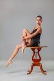 Die junge Ballerina, die auf dem Holztisch sitzt Lizenzfreies Stockfoto
