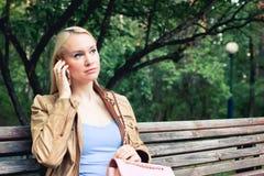 Die junge blonde Frau, die auf einer Bank sitzt und spricht telefonisch im grünen Sommerpark lizenzfreie stockbilder