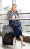 Die junge blonde Frau, die auf dem Koffer, eine Karte halten, ein Rucksack gesessen wurde, ging auf eine Reise Lizenzfreie Stockfotos