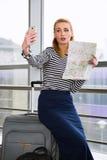 Die junge blonde Frau, die auf Koffer, eine Karte halten gesessen wird und stellt selfie Tablette her erfasst auf einer Reise Lizenzfreies Stockfoto