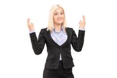 Die junge blonde Geschäftsfrau, die mit den Fingern aufwirft, kreuzte für Glück Lizenzfreie Stockfotografie