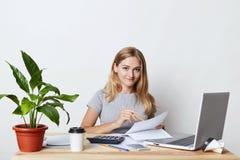 Die junge blonde Geschäftsfrau, die an ihrem Arbeitsplatz sitzt, bei der Herstellung des Geschäftsberichtes, die jährlichen Zahle Stockfotografie