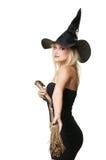 Die junge blonde Hexe mit einem Besen Lizenzfreie Stockfotos