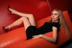 Die junge Blondine auf einem orange Sofa Lizenzfreie Stockbilder