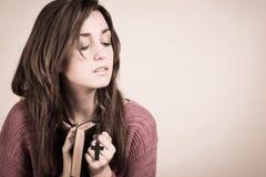 Die junge christliche Frau, die ein Kreuz durchlöchern und ein Psalm buchen Lizenzfreies Stockfoto
