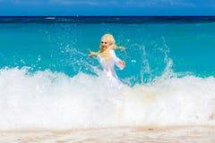 Die Junge, die mit dem langen Haar im weißen Kleid recht blond sind, genießen zu schwimmen Stockbilder