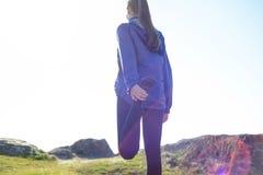Die junge Eignungs-Frau, die ihre Beine auf Rocky Trail in Sun ausdehnt, strahlt aus Weiblicher Läufer, der die Ausdehnungen im F Lizenzfreie Stockbilder