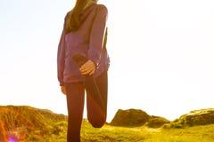 Die junge Eignungs-Frau, die ihre Beine auf Rocky Trail in Sun ausdehnt, strahlt aus Weiblicher Läufer, der die Ausdehnungen im F Lizenzfreies Stockfoto