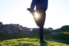 Die junge Eignungs-Frau, die ihre Beine in den Bergen in Sun ausdehnt, strahlt aus Weiblicher Läufer, der die Ausdehnungen im Fre Lizenzfreies Stockfoto