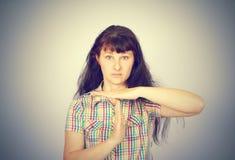Die junge ernste Frau, die Zeit heraus zeigt, gestikulieren mit den Händen Lizenzfreie Stockfotografie