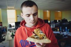 Die junge Fleisch fressende köstliche Pizza gegen einen Hintergrund von Büroräumen Schnellimbiß ein Bruch bei der Arbeit stockfoto