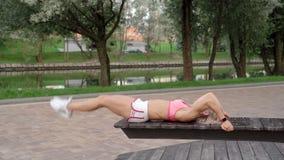 Die junge Frau, die ABS tut, knirscht im Park auf einer Bank stock video