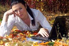 Die junge Frau arbeitet an dem Laptop Stockfoto