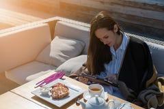 Die junge Frau, die auf dem Couchsommer-Terrassencafé sitzt, benutzt eine Tablette, Frühstück, Nachrichten, Tagebuch stockbild