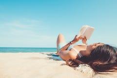Die junge Frau, die auf einem tropischen Strand liegt, entspannen sich mit Buch lizenzfreies stockfoto