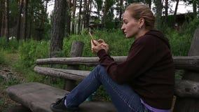 Die junge Frau, die auf Parkbank nahe Gebirgsfluss sich entspannt und sendet eine Mitteilung am intelligenten Telefon stock footage