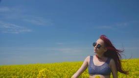 Die junge Frau, die in boho Art beeinflußt mitten in grünem Weizenfeld gekleidet wird, fängt den Wind, der nah ihre Augen zu durc stock footage