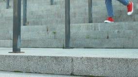 Die junge Frau, die in den Jeans und in Sportschuhen gehen unten auf Treppe gekleidet wird, Beine schließen oben stock video