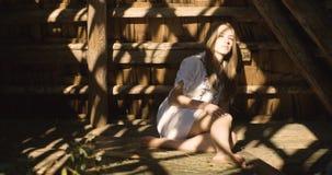 Die junge Frau, die in der Sonne l?chelt, strahlt auf dem Heu aus H?lzerne Halle 4K stock footage